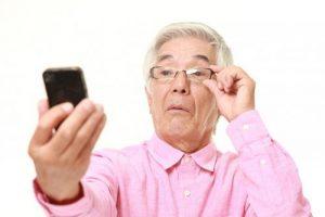 Persona mayor con presbicia mirando un móvil